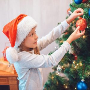 Young Girl Standing in front of a Christmas Tree